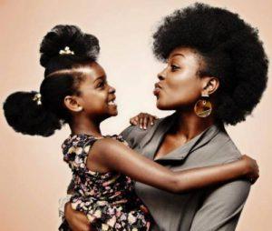 Mère tête crépue montre à sa fille tète crépue comme elles sont belles avec leur cheveux au naturel.